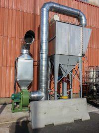 Dépoussiéreur en acier inoxydable à poches avec système écluse. Ventilateur vert relié par un réseau en gaine spiralée galvanisée. Silencieux carré au refoulement.