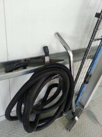 Divers accessoires pour aspirateur industriel avec différentes brosses et une rallonge flexible.